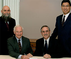 [Four men at signing ceremony]