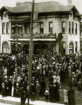 [Crowd on front lawn of venerable house]