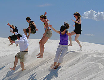 [Six of them jumping on a dune]