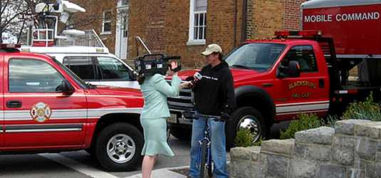[Reporter with camera interviews student in front of fire trucks]