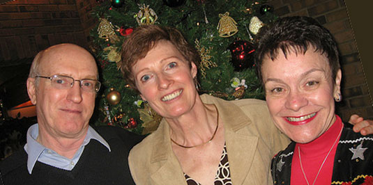 [Three happy faces in front of Christmas tree]
