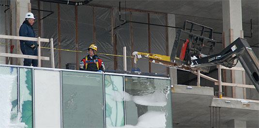 [Workers and equipment seen at an upper level]