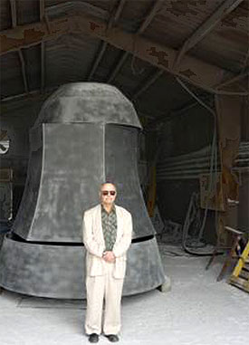 [Artist and massive bell inside barn]
