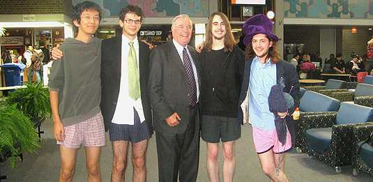 [Four young men in shorts and one old man in a suit]