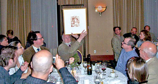 [At luncheon table, holding up certificate]