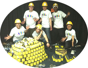 [Yellow hard hats and pyramids of yellow cans]