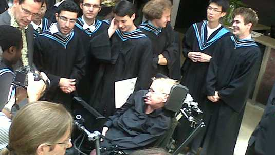 [Hawking in black surrounded by students in black]