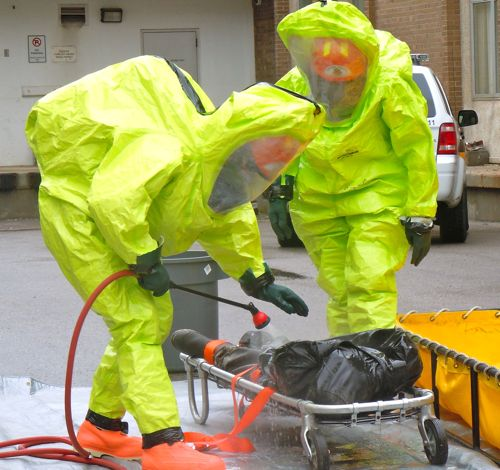 Workers in yellow hazmat suits spray a dummy victim with decontaminant