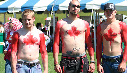 [Three guys with flags painted on their chests]