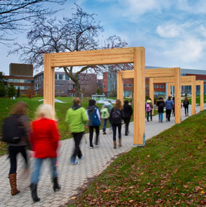 Students walk under the cedar arches at the redesigned campus gateway.
