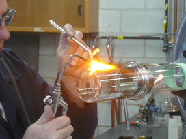 Ron Neill uses a breath-controlled device to melt glass.