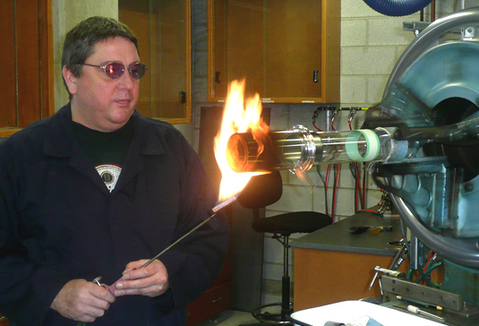 Scientific glass blower Ron Neill heats up a glass container.