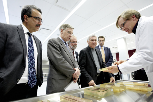 Feridun Hamdullahpur, Ken Seiling, Patrick Deane, Carl Zehr, and John Milloy look at specimens offered by Bruce Wainman in an anatomy lab.