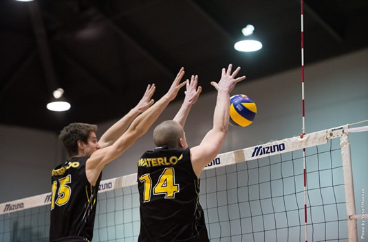 Members of the men's volleyball team jump to intercept an incoming ball.