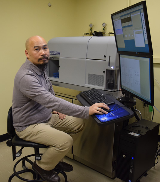 Professor Terence Tang with the laser device.