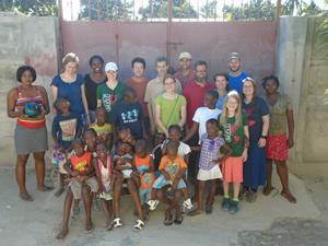 A group photo of EMI volunteers and Haitian schoolchildren.