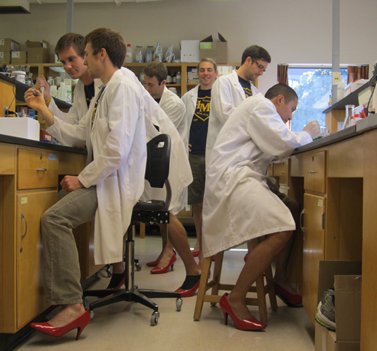 Male students wearing lab coats and red high-heel shoes.