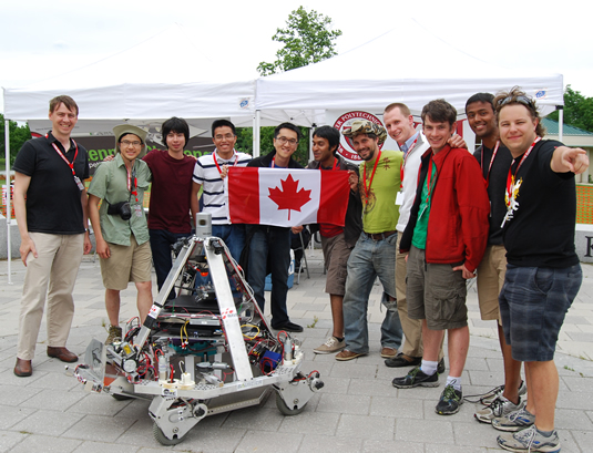 Members of the UW Robotics Team pose with the Canadian Flag and their robot.