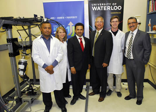 Graduate students, researchers, and government officials pose with the knee injury simulator.