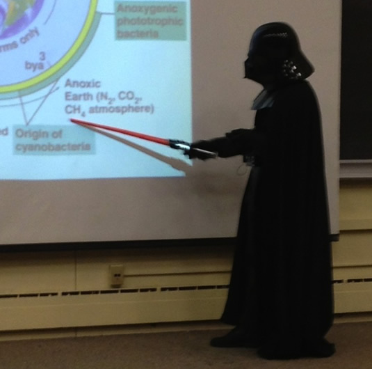 Darth Neufeld instructs his students, using a lightsaber as a pointer.