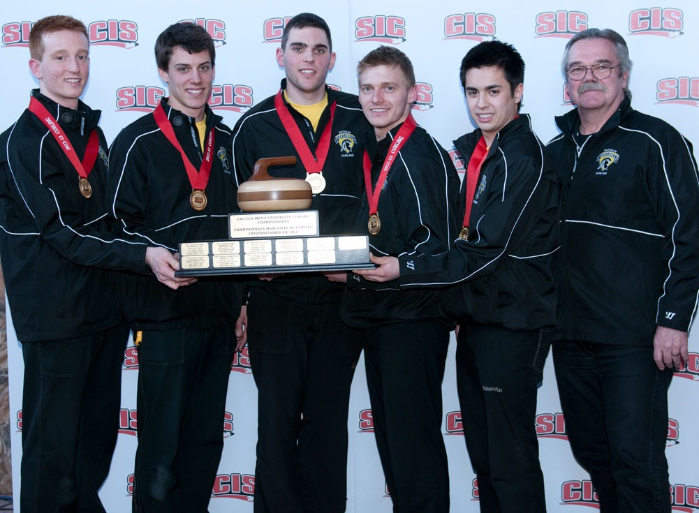 The men's curling team poses with their trophy and coach.