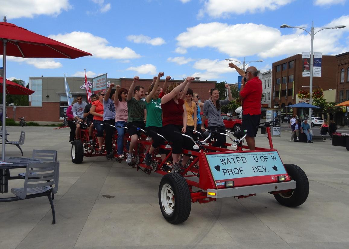WatPD team members ride a 25-person bike at Waterloo Public Square.