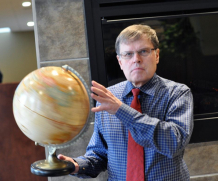 Larry smith holding a globe.