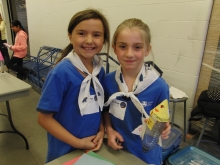 Two girl guides prepare to launch a bottle rocket.